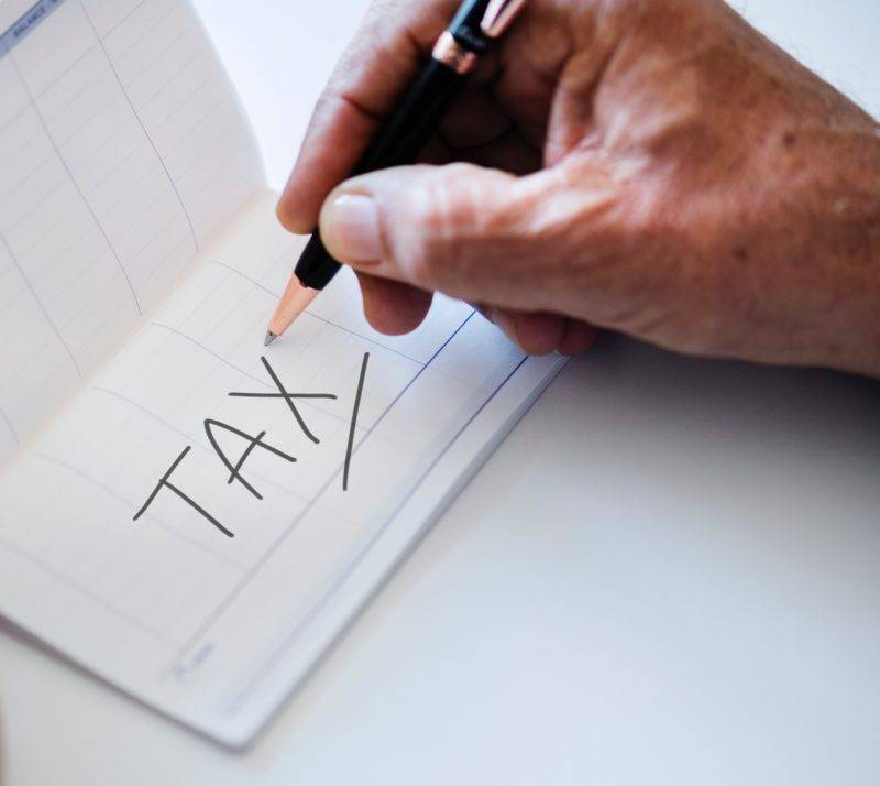 hand writing the word tax on a white paper