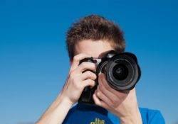 Julian vor blauem Himmel mit Kamera