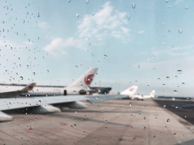 window with rain drops and some airplanes in the background