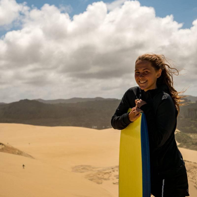 Zoe holding her Sandboard on the dunes
